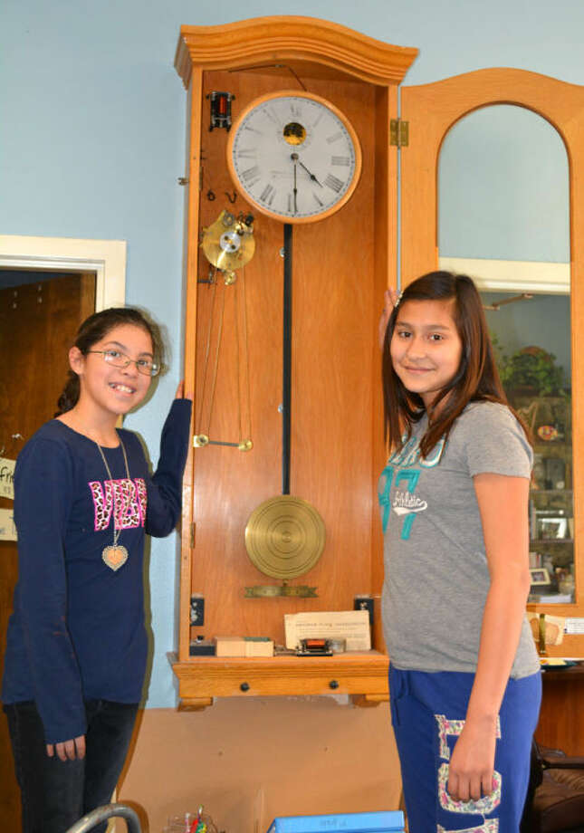 "Doug McDonough/Plainview HeraldHighland fifth graders Hannah Reyes (left) and Brittney Jimenez display the old clock in the school office that was used to operate the bells through a mechanical system using holes punched in cloth tape. While it likely dates to when the school opened in 1928, it has long since been replaced with an electronic bell system. While these two students won't be resetting this clock, which had to be wound by hand, most other clocks in the United States must be adjusted forward one hour this weekend as the nation switches to daylight saving time at 2 a.m. Sunday. The old adage for the semi-annual adjustments are to ""spring forward and fall back."" That means to turn the clock forward one hour in the spring and back one hour in the fall."