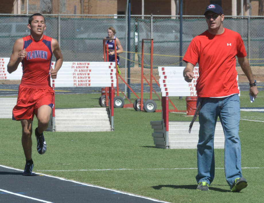 Coach Tim McCune (right) shouts instructions to Jarel Rosas (left) during the 3200-meter run at the Reagor-Dykes Bulldog Relays Friday afternoon. Rosas won the event and also took the 1600 to help his team to the meet championship. Photo: Skip Leon/Plainview Herald