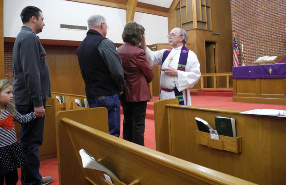 Pastor Peter Harrington of Trinity Lutheran Church, Lockney, imposes ashes and oil in the sign of the cross on the foreheads of parishioners. Photo: Gail M. Williams | Plainview Herald