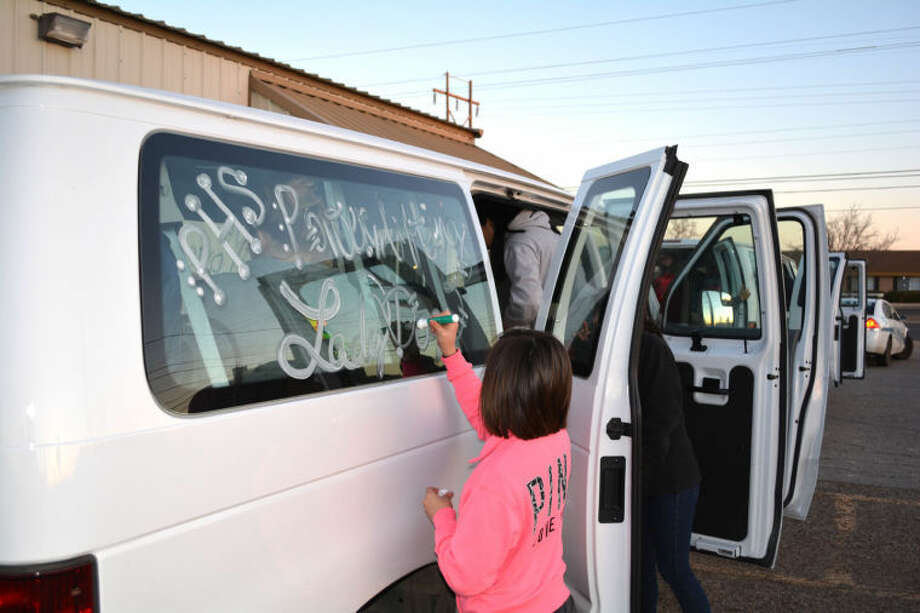 Plainview High Lady Bulldogs powerlifter Kimberly Balderas paints the windows of one of two school vans early Wednesday before the team left Plainview for the state contest.The team which qualified 12 lifters for the state meet received a police escort as they left Plainview at 8 a.m.