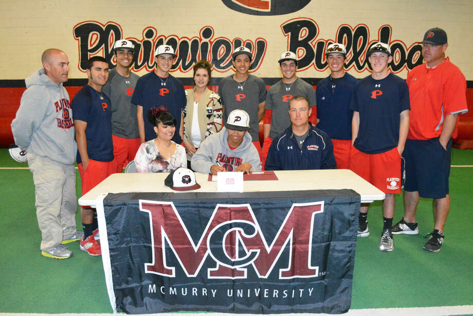 Plainview's Danny Martinez (center, front) signs a letter of intent to play baseball at McMurry University. Flanking Martinez are his mom, Rachelle Martinez (left) and Plainview baseball coach Jimmy Webster (right). Standing (from left) are Bulldogs assistant coach Shawn Stanek, and Bulldog players Sean Sanchez, Ryan DeLeon, J.D. Armijo, friend Jasmine Armijo, and players Michael Soliz, Brent Silvas, Jared Rodriguez, Brennen Carreon and assistant coach Brandon Gilliland. Photo: Skip Leon/Plainview Herald
