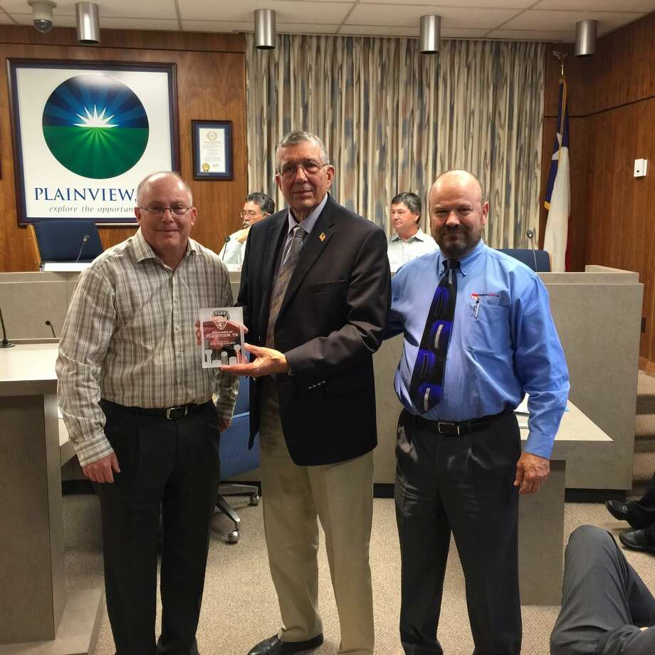 "Tnemec representatives Leonard Nail (right) and Lane Salvato (left) present Plainview Mayor Wendell Dunlap with a special award for the City's top-12 finish in their annual ""Tank of the Year"" contest, which featured Plainview's two new water tanks."