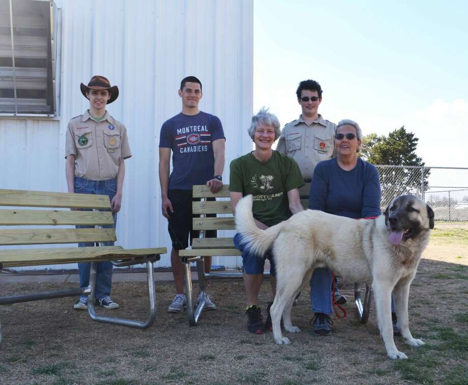 Doug McDonough/Plainview HeraldEagle Scout candidate Ethan Andersen (standing center) delivered two benches to PAWS and the City Animal Shelter on Wednesday to complete his Eagle Scout Service Project, an advancement requirement to achieve Scouting's highest rank. He is assisted by fellow Troop 253 members Evan (left) and Eli Puckett. Trying out the new benches are Cynthia Davidson and Donna Austin of PAWS, accompanied by Duke. The benches will be in the fenced exercise yard at the shelter to allow a comfortable environment for people to interact with prospective pets. Andersen, 17, is a senior at Plainview High School and the son of Nancy and Robert Andersen of Plainview. He was able to assemble the benches with the help of TD&J Auto, which crafted the frames, and McCoy's Lumber, which donated treated lumber and hardware to construct the benches.