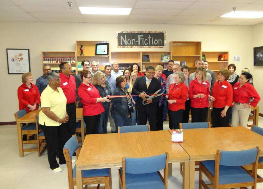 RoiJon Johnson/Plainview HeraldHouston School Principal John Gatica uses a pair of hedge clippers to snip a ribbon marking the formal opening of the first onsite library at Plainview's alternative school. The ribbon cutting, held by the Plainview Chamber of Commerce and its Ambassadors Committee on Tuesday, coincided with a Business After Hours mixer at the Hale County Literacy Council, which has offices on the campus. The library was made possible through generous donations from the Literacy Council, Walmart Distribution Center and various individuals.