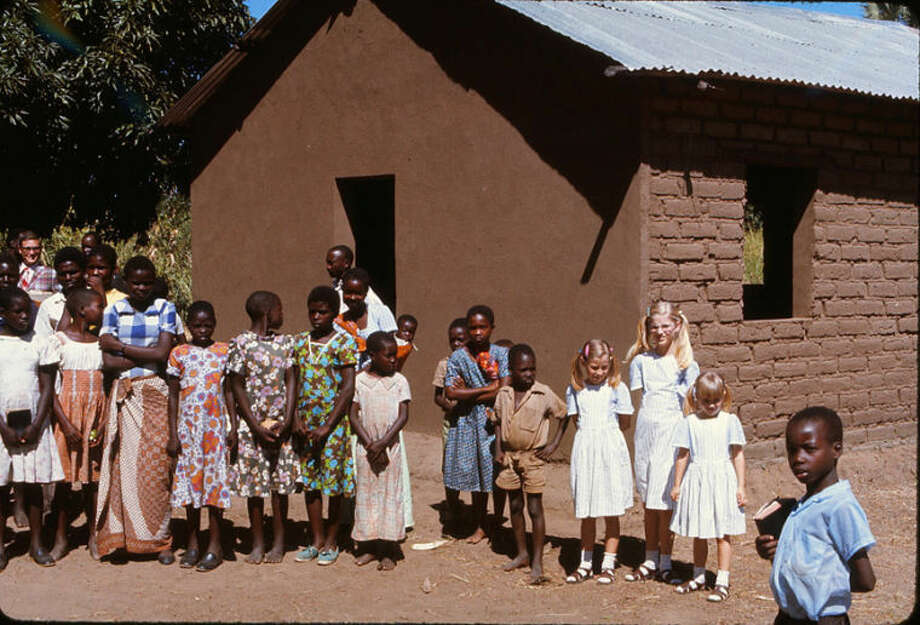 Gene Meacham's daughters, dressed in their Sunday best, with the members of a village church. Congregations strove to add a metal roof to their churches. Photo: Courtesy Photo | Gene Meacham