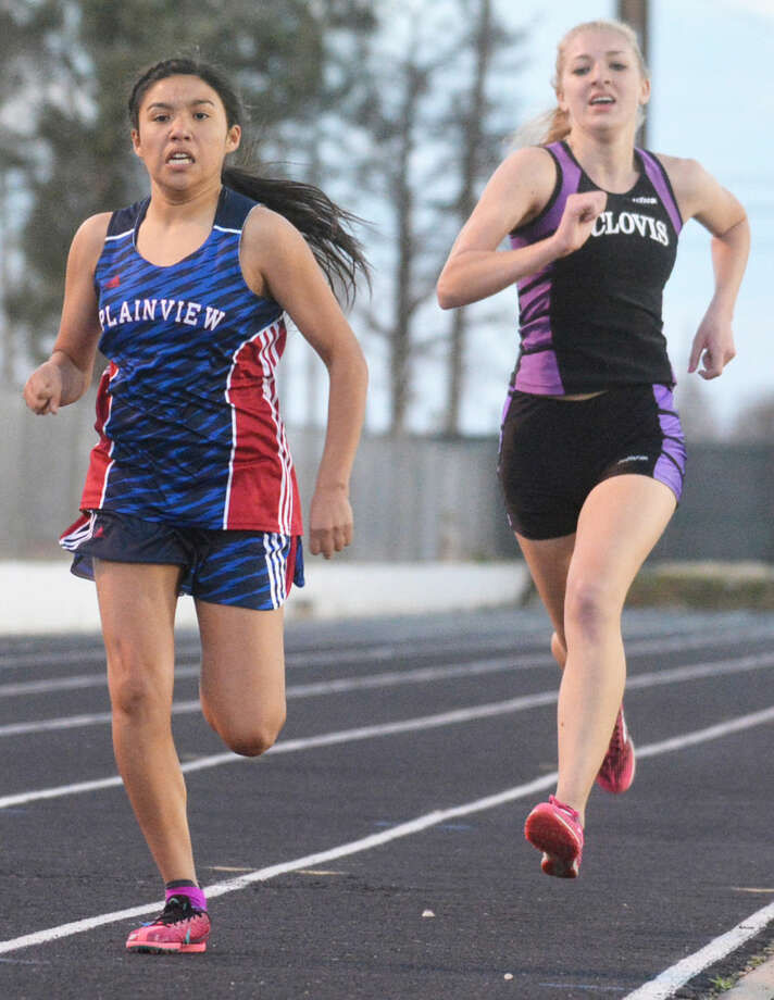 Plainview's Klarysa Godino fends off a challenge by Clovis (N.M.) runner Holly Steinle in the home stretch of the 1600-meter run at the Reagor-Dykes Bulldog Relays Friday. Photo: Skip Leon/Plainview Herald