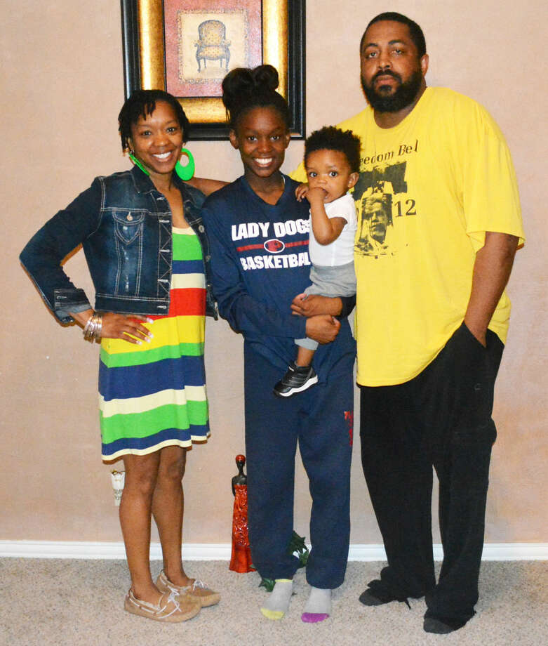 "Plainview track athlete Kaizha Roberts, center, holds her brother, 11-month-old Bailor J. Myers as she is flanked by her parents, LaTosha Myers, left, and Bennie ""B.J."" Myers, right. Roberts, a Plainview High School sophomore, will have a chance to go to Australia and compete in a track meet in July as part of the Down Under Sports program. Photo: Skip Leon/Plainview Herald"
