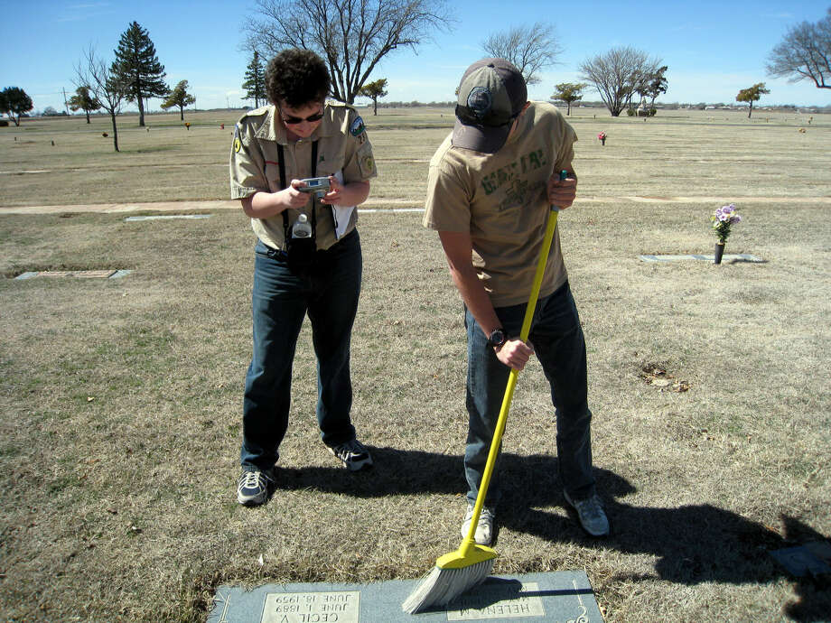 Service ProjectJohn Sigwald/Unger Memorial LibraryEagle Scout candidate Eli Puckett takes a photo of a headstone in Plainview Memorial Park cemetery after Glen Fikes sweeps away grass. For his Eagle Scout service project, Puckett is taking photographs of the headstones in Block C of the cemetery. His 2,000 photographs will be entered into the Hale County Cemetery Records online database, which was created by members of the Hi-Plains Genealogical Society and Unger Memorial Library. A member of Boy Scout Troop 253, Puckett is the son of Kevin and Beverly Puckett.