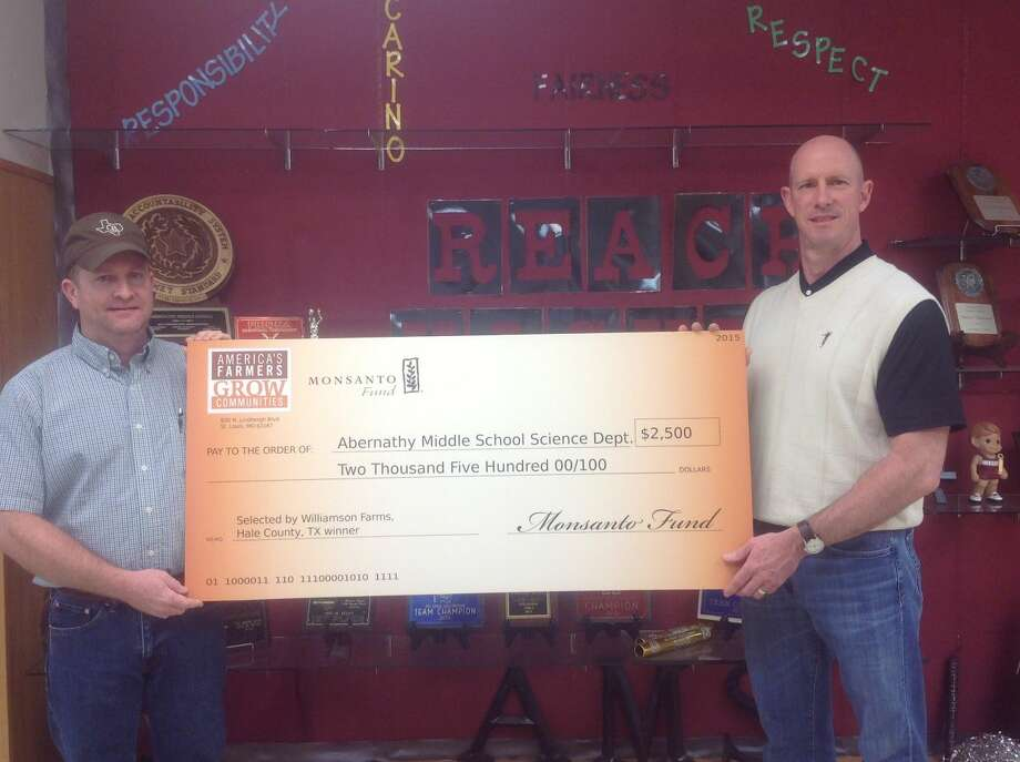 Hale County farmer Matthew Williamson presents Abernathy Middle School Principal Bill Black with an ceremonial check signifying a $2,500 to the school's Science Department from America's Farmers Grow Communities which is sponsored by the Monsanto Fund.