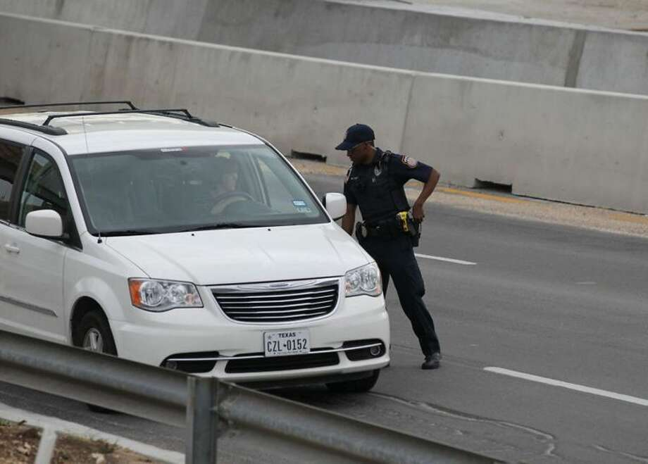A police officer checks drivers' IDs outside the main gate at Fort Hood, Texas, after a shooting at the Army base on Wednesday, April 2, 2014. (Deborah Cannon/Austin American-Statesman/MCT) Photo: Deborah Cannon