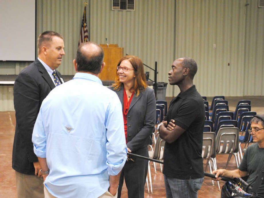 Plainview/Hale County Industrial Foundation Executive Director Kevin Carter (left), Dr. Katharine Hayhoe and actor Don Cheadle speak with a documentary producer following Thursday's climate meeting at the Ollie Liner Center. A sound technician kneels at lower right while recording the exchange. Photo: Ryan Crowe/Plainview Herald