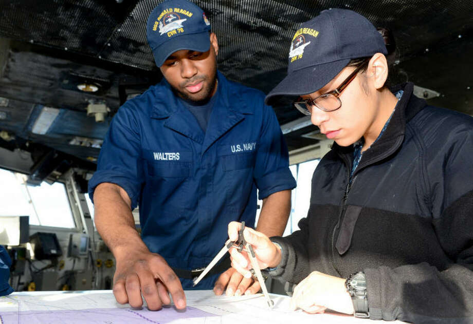 Quartermaster Seaman Yahshemi Walters (left) and Seaman Stephanie Hernandez plot the ship's location from the bridge of the aircraft carrier USS Ronald Reagan (CVN 76). Ronald Reagan is currently underway, conducting tailored ship's training availability. Photo: Photo By Mass Communication Specialist 3rd Class Charles D. Gaddis IV
