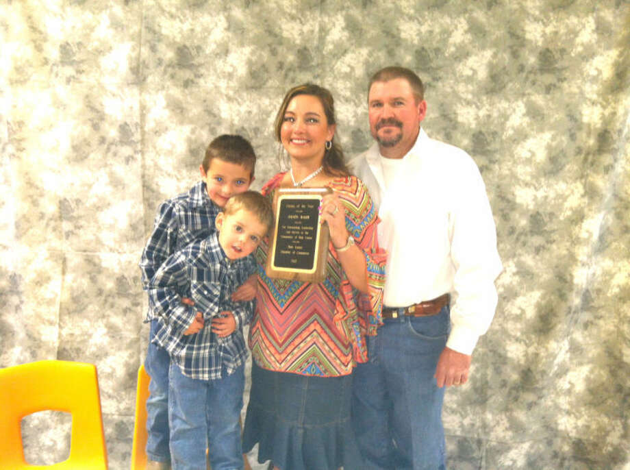 Wendy Baker along with her family, husband Glenn and sons Ryan and Brady, show off her plaque after she was introduced as Hale Center's Citizen of the Year on Saturday.