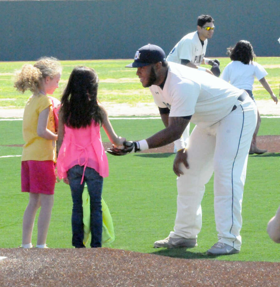 Wayland first baseman Gaby De La Cruz greets two Edgemere Elementary students who took the field with him prior to Tuesday's game against University of the Southwest at Wilder Field. Photo: Kevin Lewis/Wayland Baptist University
