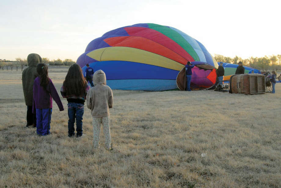 Xavier Gomez (left), Mikayla Gomez, Julissa Gomez and Majin Gomez watch as the Quadnickle crew from Amarillo prepares their balloon, Serenity, for launch. in the background, the Amarillo National Bank crew gets their balloon ready at Saturday's Fool's Cup balloon launch in Plainview. Photo: Richard Porter/Plainview Herald
