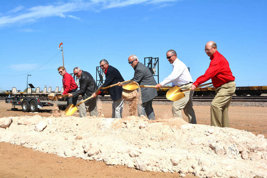 As a line of trunks in the background brings crashed rock to serve as a base for wind turbine blades arriving by rail, local representatives join officials of Transportation Technology Services to formally break ground Tuesday on its distribution center off County Road Y and US-70. Amid a beehive of activity in front of the BNSF siding, those wielding the golden shovels are County Judge Bill Coleman (left), TTS General Manager John Dalman, Mayor Wendell Dunlap, TTS Marketing Director Kreigh Valkenaar, Plainview-Hale County Economic Development Corp. President Danny Glenn and PHCEDC Executive Director Mike Fox.