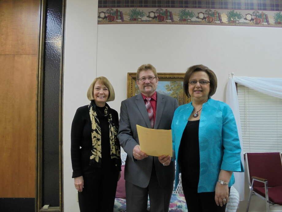 Hale County Judge Bill Coleman hands a proclamation naming April 7 as National Service Recognition Day to Linda Milner Shipp (left) and Irma Shackelford, representing Runningwater Draw RSVP.