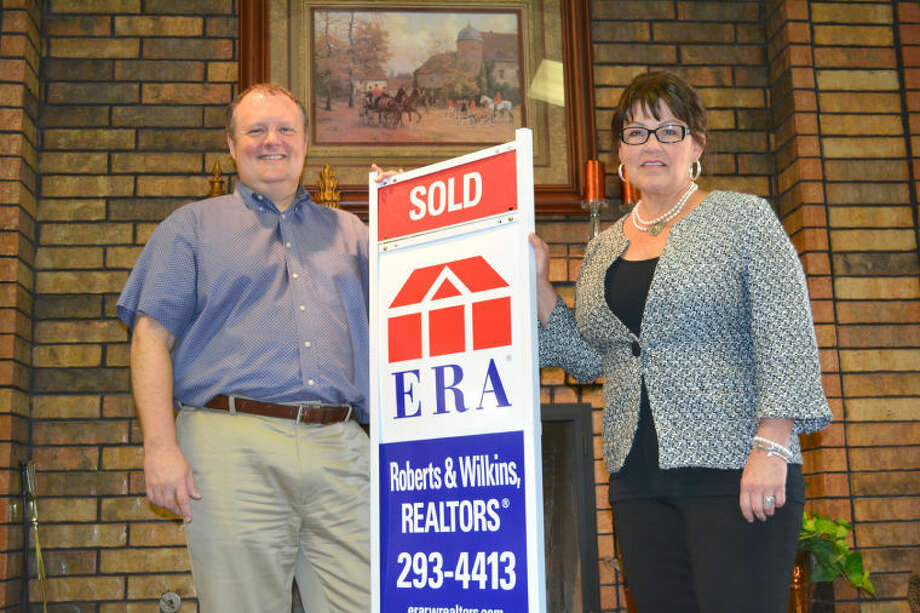 Doug McDonough/Plainview HeraldDrury Roberts and Debbi Wilkins of ERA Roberts & Wilkins show off one of their signs while awaiting delivery of the prestigious Jim Jackson Memorial Award. The local real estate office is the 2013 winner of the national excellence in customer service award.
