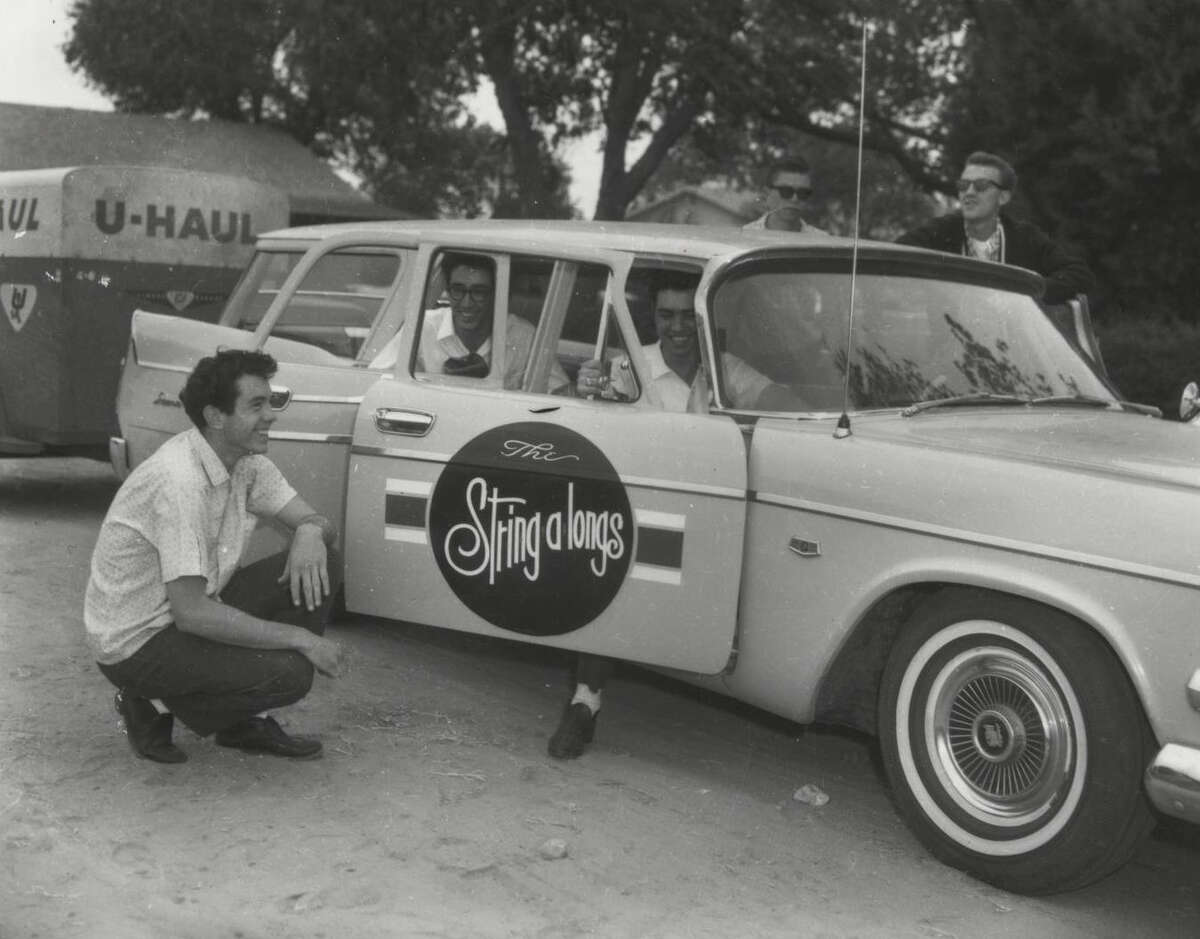 Above Keith McCormack (left) kneels next to the String-A-Long station wagon before touring with his band.
