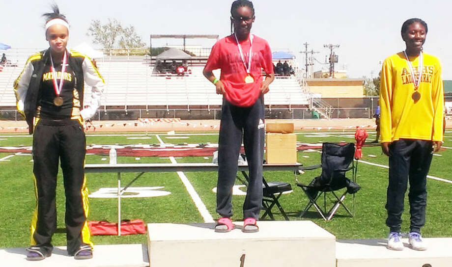 Kaizha Roberts (center) stands on the platform at the regional meet wearing the gold medal she earned for winning the triple jump. Photo: Courtesy Photo