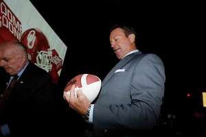 CORRECTS THE COACHES NAME TO BOB STOOPS, AND NOT MIKE GUNDY AS ORIGINALLY SENT - Oklahoma head coach Bob Stoops signs a football during the Big 12 college football media days in Dallas, Tuesday, July 19, 2016. (AP Photo/LM Otero)