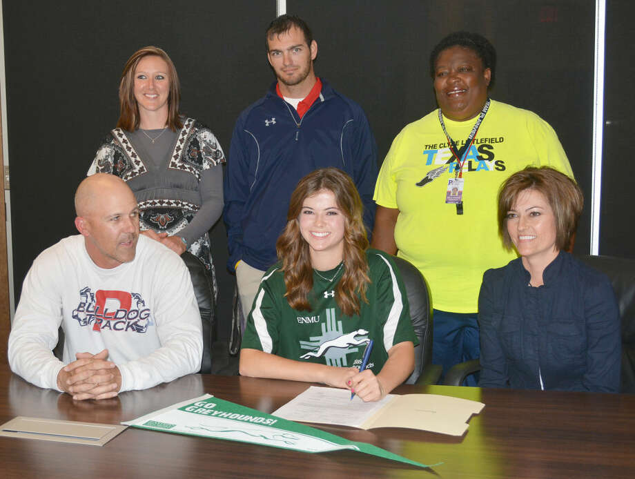Plainview High School senior Brooke Walker (seated center) signs a letter of intent Tuesday to run track at Eastern New Mexico University in Portales. She is flanked by her parents, Lee Walker (left) and Sonia Walker (right). Standing (from left) are assistant track coaches Krystal McCune, Tim McCune and Della Riggins. Photo: Skip Leon/Plainview Herald