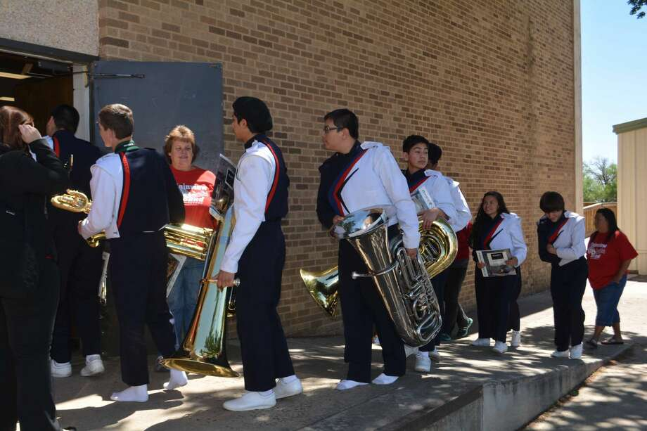 Plainview Band Booster representative Tammy Waller holds a door open for members of the Plainview High Non-Varsity Red Band on Tuesday as they file into a rehearsal room at Wayland's Harral Auditorium for the UIL Concert and Sightreading Contest. All four PHS bands competed Tuesday, along with area 1A and 2A bands. The two-day contest concludes today with more 2A, 3A and 4A bands.