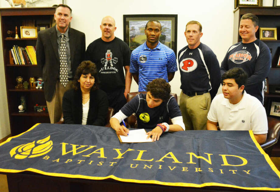 Plainview High School senior Jon Luna (seated, center) signs a letter of intent Wednesday to play soccer at Wayland Baptist University. Seated, flanking Luna, are his mom Cristina Luna (left) and his brother Javier Luna (right). Standing (from left) are Plainview High School Principal Tye Rogers, PHS track head coach Lee Walker, WBU assistant soccer coach Shermon Gardner, PHS assistant track coach Matt Horton and PHS boys athletic director and football head coach Ryan Rhoades. Photo: Skip Leon/Plainview Herald