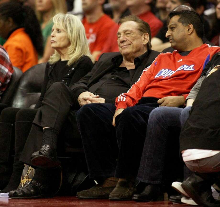 Donald Sterling, center,, owner of the Los Angeles Clippers, watches a Clipper game against the Boston Celtics at Staples Center in Los Angeles earlier this season. At left is Sterling's wife, Rochelle. Sterling was given a lifetime ban from the NBA for racist comments he made at a game recently. Photo: Gary Friedman/Los Angeles Times/MCT