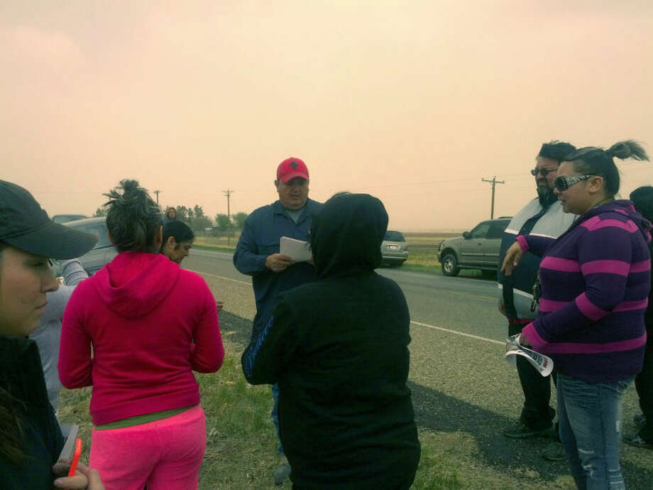 Angel Pena, father of missing 26-year-old Plainview man Andrew Pena, hands out fliers to volunteers who helped search for clues to this son's disappearance along FM 400 Tuesday. Photo: Homer Marquez/Plainview Herald
