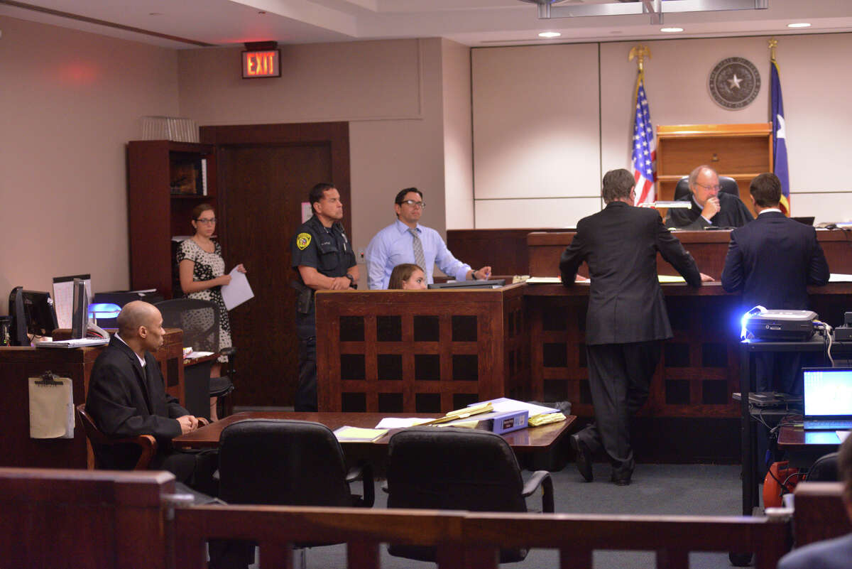 Dominique Green, (far left) sits at the defense table as attorney's confer with Judge Sid Harle at the beginning of his capital murder trial Tuesday.