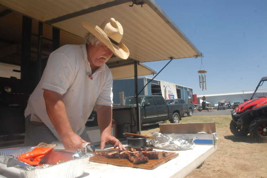 "Plainview BBQ cook Chris Carter slices some mouth-watering ribs for the second annual Mark Marley Go Big or Go Home State Championship BBQ Cook Off Saturday. Carter and his team ""Happy To Be Here"" joined 37 teams from the area seeking to take the top prizes in the IBCA sanctioned cookoff. Check out myplainview.com for more shots of the competition and check out Tuesday's edition for the winners."