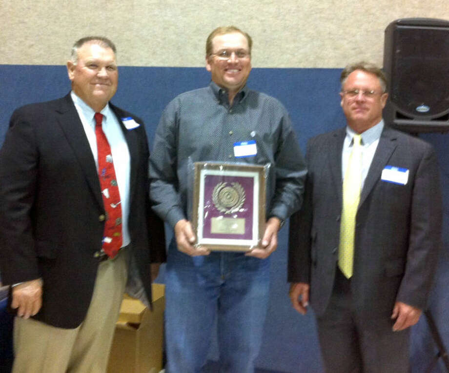 Courtesy PhotoRob Bass, Hale County's Outstanding Conservation Farmer for 2013, receives a plaque Tuesday at the Area I Conservation Honors Banquet from Rickey James of Plainview (left), president of the Association of Texas Soil & Water Conservation Districts, and Scott Buckles of Stratford (right), vice president.