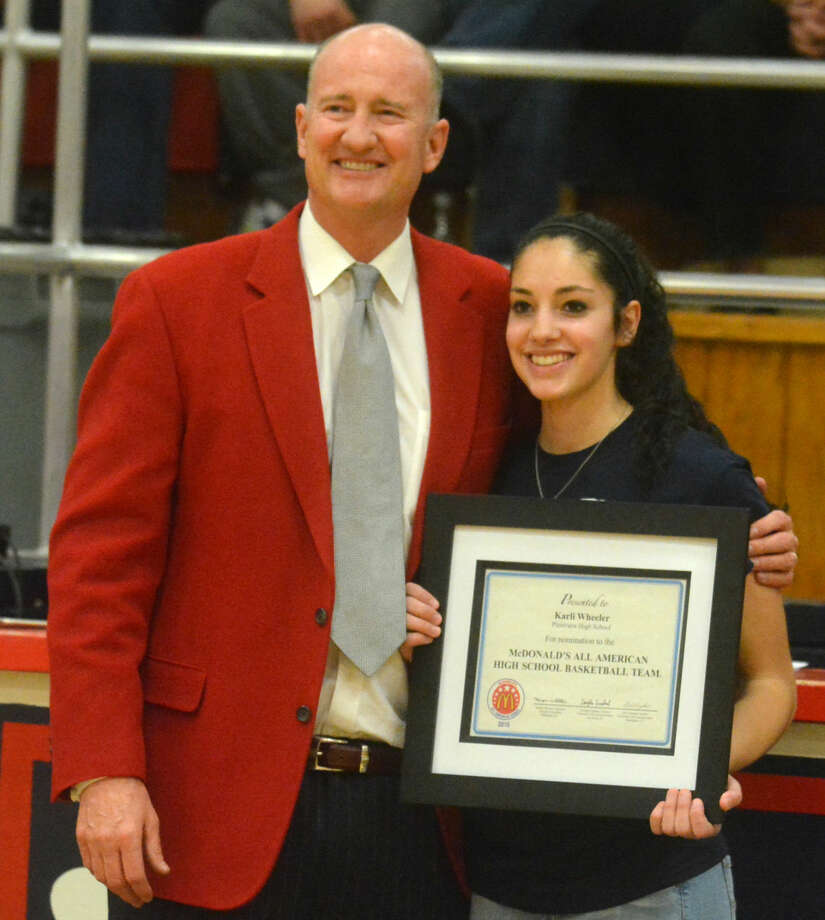 Plainview's Karli Wheeler (right) holds her award for being nominated to the McDonald's All-American team, which was presented to her by her coach, Danny Wrenn (left) after the final home game of the season. Wheeler's latest honor was being named the Class 5A Player of the Year in the state of Texas by the Texas Association of Basketball Coaches (TABC). Photo: Skip Leon/Plainview Herald