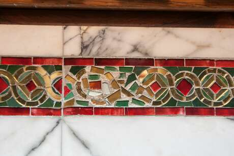 A glass mosaic tiled bench still bears the scar of the bullets from nearly a century ago, in the form of a poor repair job, in courtroom one of the 9th Circuit Court of Appeals. On April 23, 1918, shots rang during the Fraz Bopp-Wilhelm von Brincken trial. Ram Singh, a defendant turned government witness, shot and killed Ram Chandra, also a defendant and leader of the Indian Revolutionary party. James P. Holohan, a United States Marshall, standing in the rear, climbed on the nearest seat, drew his revolver, and shot and killed Ram Singh. Photo: Douglas Zimmerman