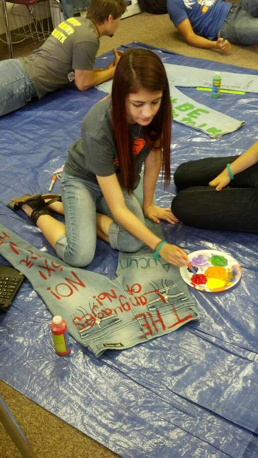 Tulia High School junior Destany Whiteley paints a pair of jeans with sexual assault prevention slogans leading up to Denim Day. Photo: Courtesy Photo
