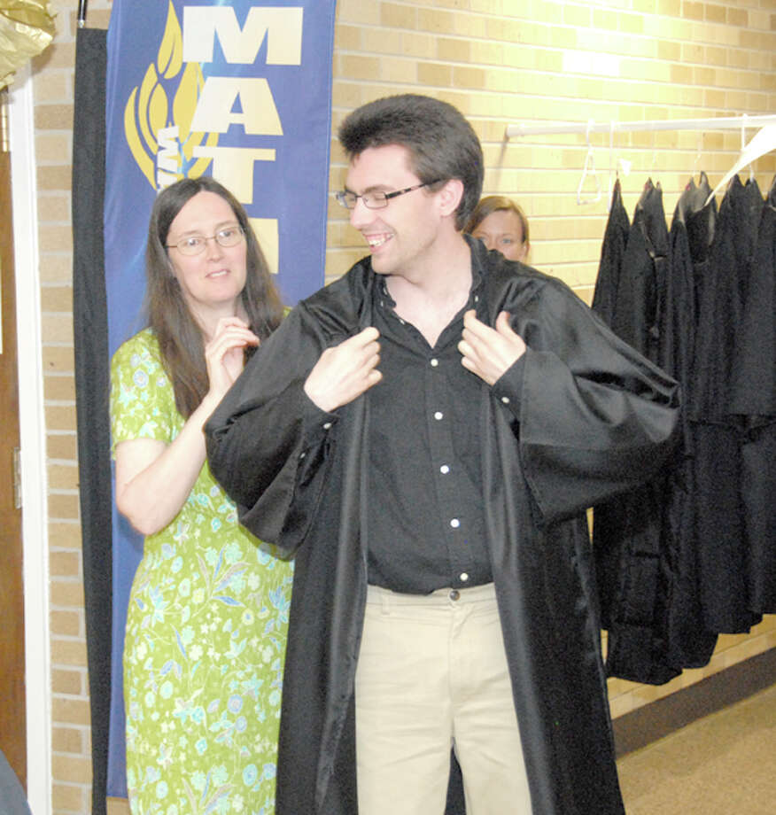 Brian Adamson receives his graduation robe from mother Dr. Elise Adamson during a robing ceremony for the Wayland Baptist University School of Mathematics and Sciences. Adamson graduated Saturday with a Bachelor of Science Degree with Honors in mathematics and chemistry.