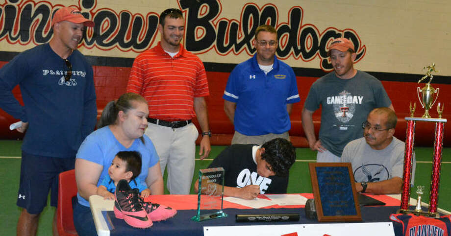 Plainview High School senior Joey Gonzales (seated, center) signs a letter of intent Monday to run track at Wayland Baptist University. Looking on are (seated, left) his mom Sandra Molina holding Joey Gonzales III, and (seated, right) his dad Joe Gonzales. Standing in the back row are (from left) Plainview High School track head coach Lee Walker, PHS cross country head coach and assistant track coach Tim McCune, Wayland Baptist University assistant track coach Brian Whitlock and PHS assistant track coach Matt Horton. Photo: Skip Leon/Plainview Herald