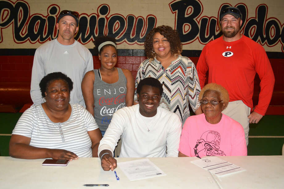 Plainview's Khalid Riggins (seated, center) signs a letter of intent Wednesday to attend Eastern New Mexico University in Portales and compete on the track team. Also seated are Della Riggins (left), his aunt and an assistant track coach, and his grandmother, Ruby Riggins (right). Standing are, from left, Plainview track head coach Lee Walker, Khalid's cousin Adeva Jennings, his aunt Marleta Davis, and Jodi LaFrance, the Plainview track throwing coach. Riggins throws the discus. Photo: Skip Leon/Plainview Herald
