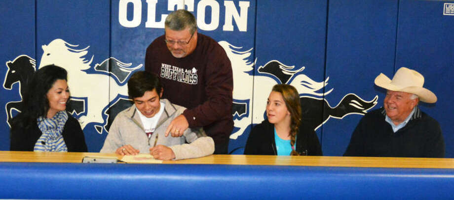 Olton High School senior J.R. Sullivan signs a letter of intent at the school gym Tuesday to run track at West Texas A&M University next season. Looking on are seated (from left) Elsa Sullivan, J.R.'s mom; Carolyne Sullivan, his sister; and Bryan Sullivan, his dad. Standing is Olton athletic director Kent Torbert, who coached Sullivan in football and track. Photo: Skip Leon/Plainview Herald
