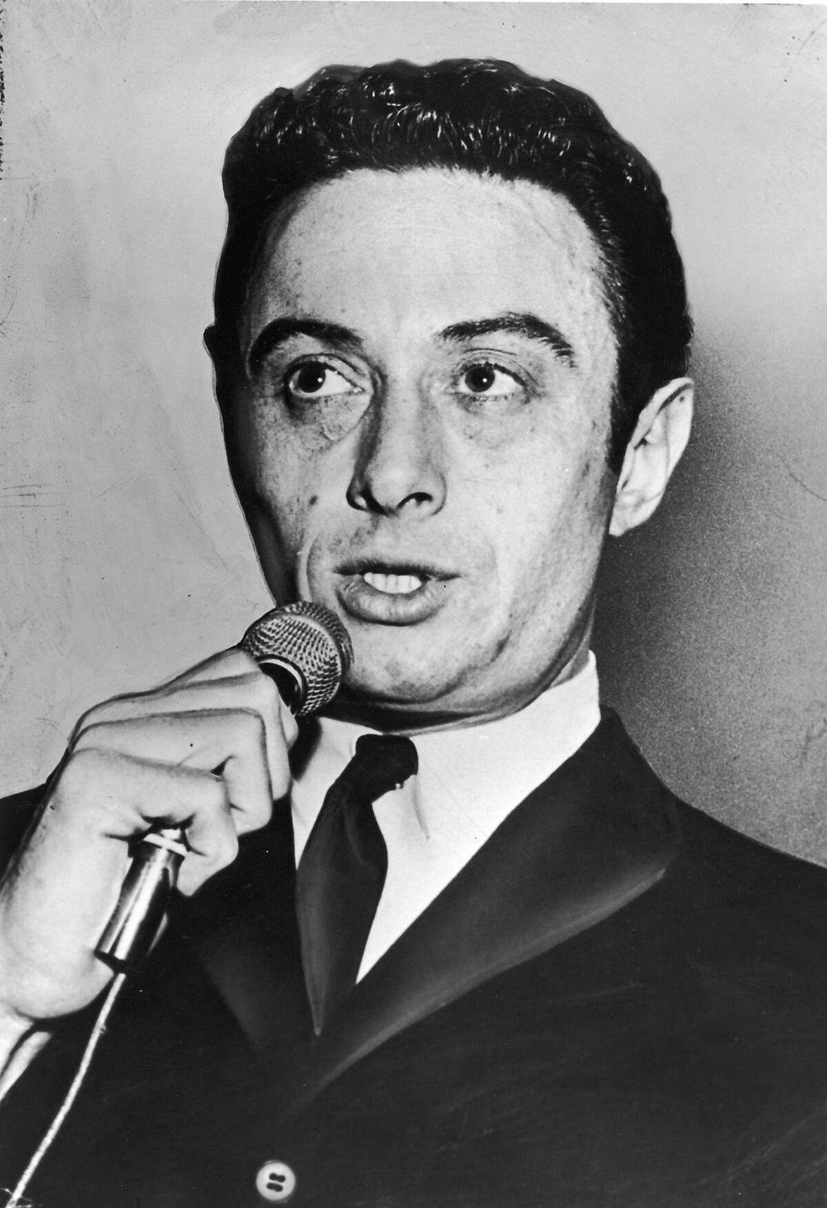 American comedian Lenny Bruce (1925 - 1966) holds a microphone while performing, 1950s. (Photo by Hulton Archive/Getty Images)