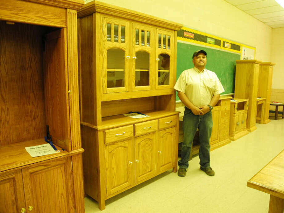 Edward Vuittonet, who received the ITEEA Teacher Excellence Award for 2013-14, stands next to a china cabinet built by Brennon and Breana Amador in Kress High School's ITE class. Photo: Gail M. Williams | Plainview Herald