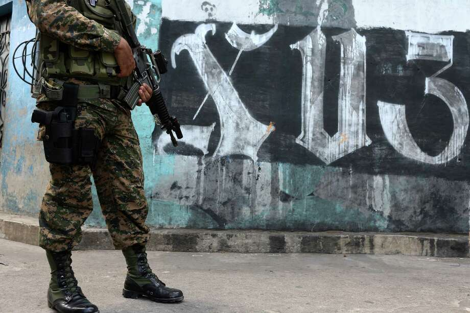 Members of the Salvadoran military and the Policia Nacional Civil patrol the alleys of the Colonia Jardin de Don Bosco in San Salvador, El Salvador, Wednesday, April 6, 2016. The neighborhood, like others in El Salvador, is home to two of the most powerful gangs in the country, MS-13 and Barrio 18. During their security detail, the soldiers will question young men and women in order to ascertain if they have a gang affiliation. There were no arrests during the operation. Photo: JERRY LARA, San Antonio Express-News / © 2016 San Antonio Express-News