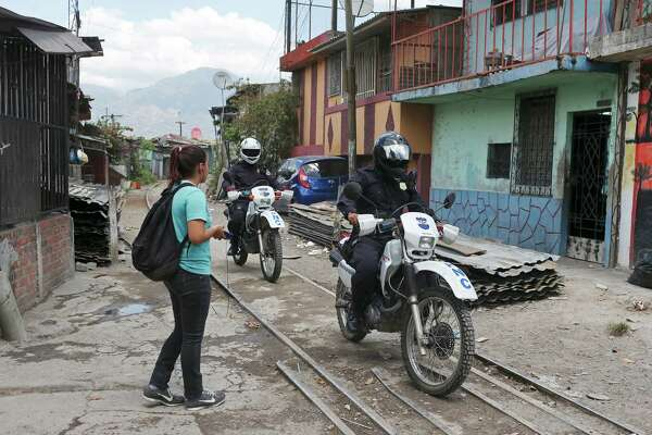 Members of the Policia Nacional Civil ride the rail line while on patrol with Salvadoran military personnel in the Colonia Jardin de Don Bosco of San Salvador, El Salvador, Wednesday, April 6, 2016. The neighborhood, like others in El Salvador, is home to two of the most powerful gangs in the country, MS-13 and Barrio 18. During their security detail, the soldiers will question young men and women in order to ascertain if they have a gang affiliation. There were no arrests during the operation.