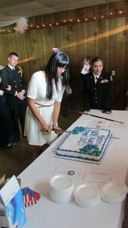 Following tradition, Plainview High School NJROTC member Cynthia Luna uses a saber to cut through cake while Brandy Arroyos watches during the PHS NJROTC banquet. Photo: Courtesy Photo