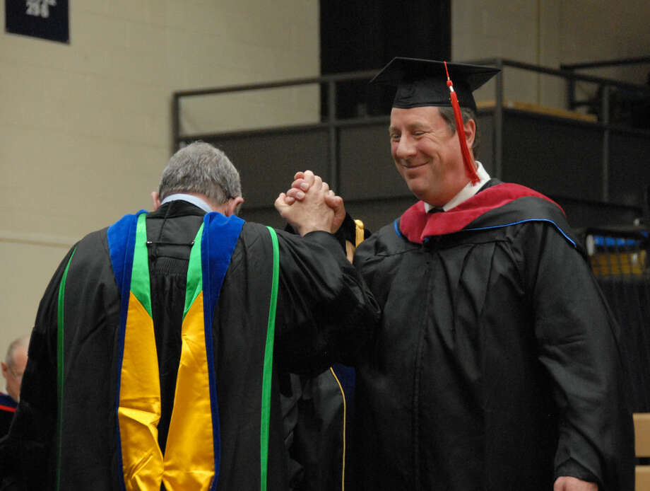 Damon Pearce, of Clovis, gets a high-five from Dr. Paul Sadler, dean of the School of Religion and Philosophy, after receiving his hood for the Master of Divinity degree. Pearce is the first person to receive the degree from Wayland.