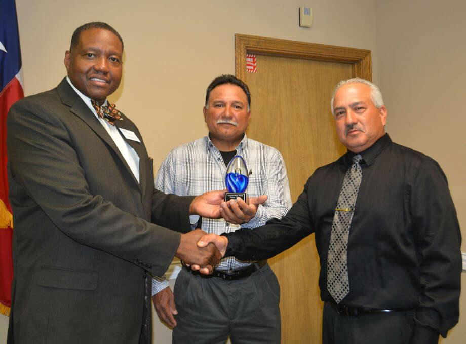 SBA District Director Calvin Davis (left) presents the regional Minority Small Business Champion of the Year award to Arturo Samaron of Amarillo and Roger Rosales of Plainview, owners of Elite Transmission & Distribution Electric, Inc. The award come during a special presentation Wednesday.