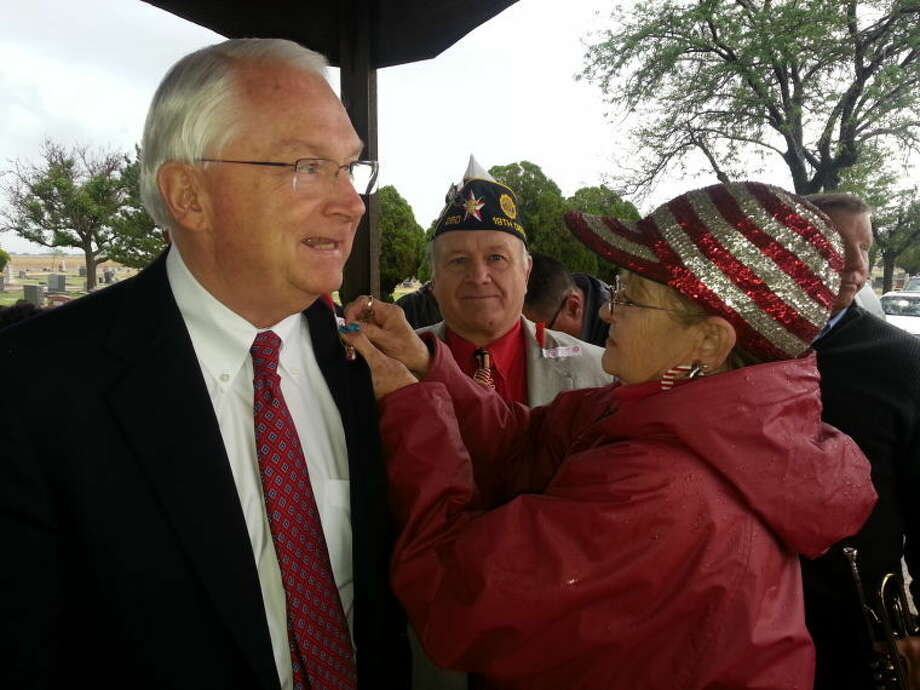 Ralph Langley watches on as American Legion Auxiliary Post 260 Chaplain Jerree McKeeman pins a Memorial Day poppy on U.S. Rep. Randy Neugebaur. On Monday, a crowd braved the elements to honor the nation's valiant defenders during Plainview Memorial Day services. Check out more photos of the ceremony on myplainview.com. Photo: Courtesy Photo/Dr. Charles Starnes