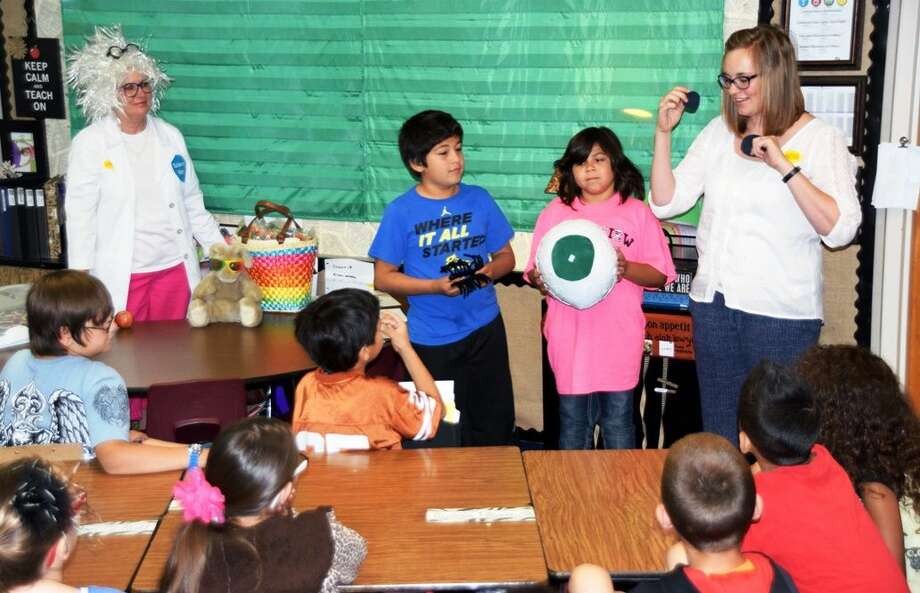 "Science NanaJan Seago/Plainview ISD""Science Nana"" Andrea Ingram (left) visited La Mesa Elementary third grade classes on Tuesday and brought along optometrist Dr. Lindsey Mathis (right) to share a lesson on eyes and how they work, and the foods that help our vision. Students assisting in constructing a model of the eye are Michael Rivera and Jazlynn Hernandez. Science Nana has been visiting the campus with science lessons for more than eight years. On this visit, she brought the students sunglasses to reinforce the need to protect eyes from the sun. Dr. Mathis gave students eyeball cookies to add a bit of fun to her lesson."