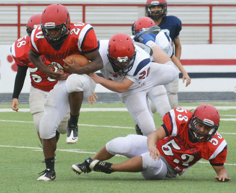 A runner high-steps his way through the line as a defender leaps over a prone offensive lineman and tries to make the tackle during the Plainview Bulldogs' Red/White Spring Football Game last week. Photo: Skip Leon/Plainview Herald